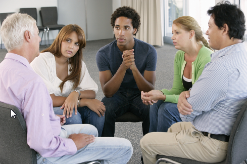 An image of 5 people sitting in a circle- depicting a support group setting.